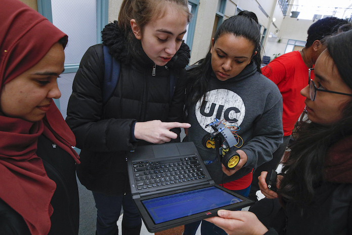 four female students of diverse backgrounds working on a programmable model car